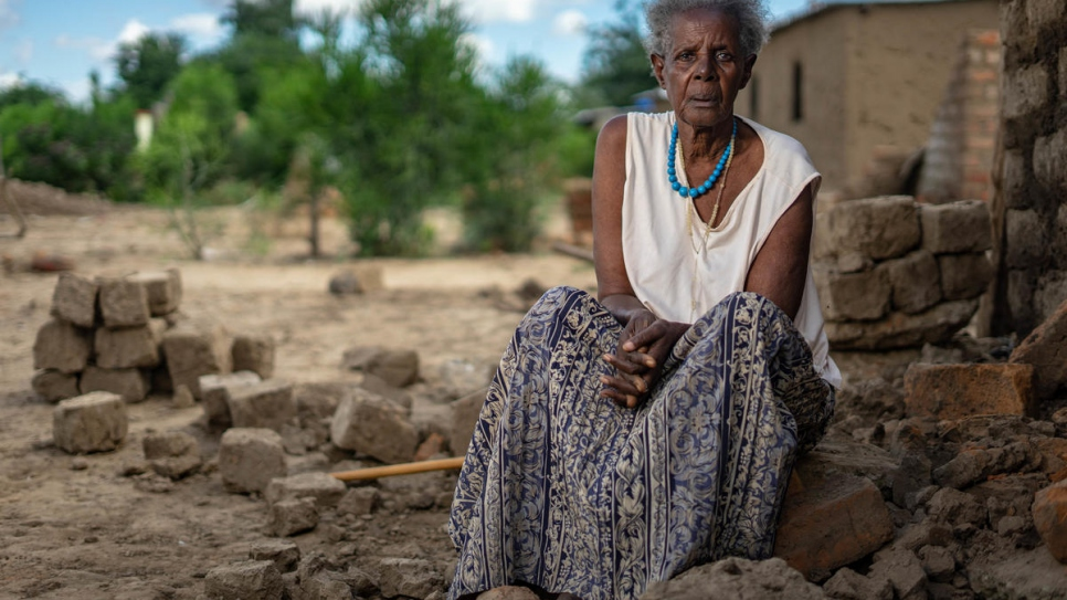 Rwandan refugee Magdalena Niragire sits by the rubble of her home partly demolished by torrential rains that pounded Tongogara refugee camp, Zimbabwe.
